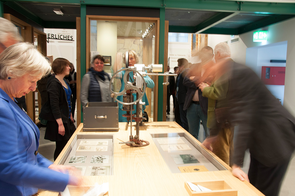 "<span class=""deutsch"">Eröffnung: Besucher an der »hands-on« Dosenverschlussmaschine</span><span class=""englisch"">Opening: Visitors testing the »hands-on« canning device</span>"